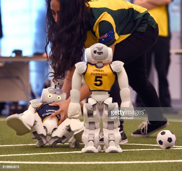 Amri Chamela catches a soccer robot from falling in Sydney on July 21 as Australias fivetime world champions of robot soccer the University of New...