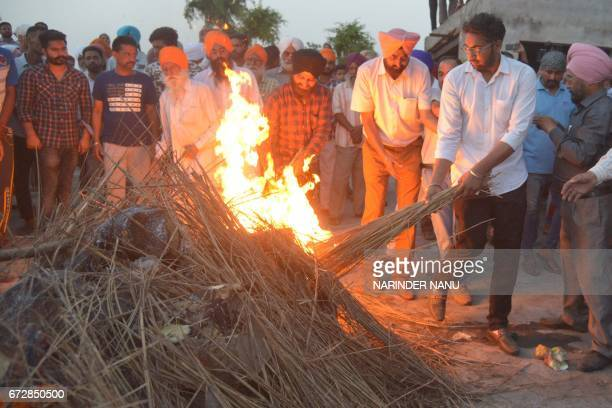 Amritbir Singh son of Indian Central Reserve Police Force personnel Raghbir Singh lights his funeral pyre in Sathiala village some 45km from Amritsar...