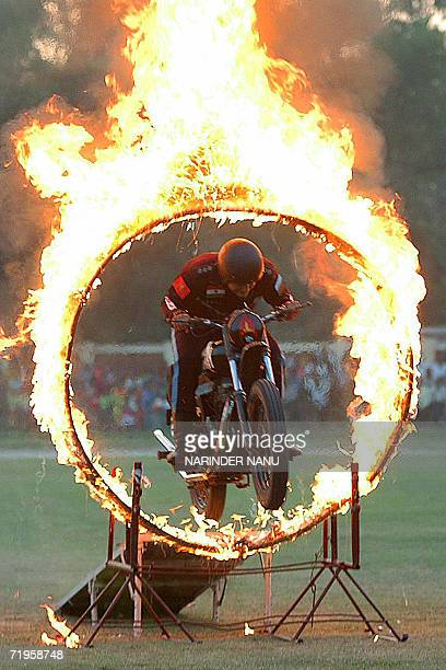 A member of The Indian Army motorcycle display team rides his motorcycle through a 'Ring of Fire' as he shows off his skills during a 'Dare Devils'...