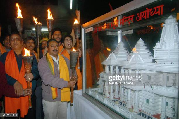 Indian activists of the Hindu Bajrang Dal Party hold torches while standing behind a model of Ram Temple during a procession 'Shorya Divas' held on...