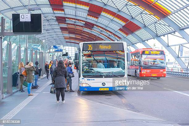 Amsterdam bus station with people boarding the busses