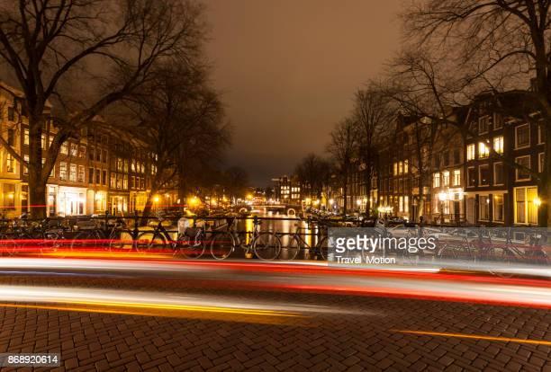 Pont-canal d'Amsterdam avec sentiers de lumière dans la nuit