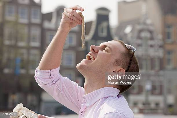 amsterdam tourist eating herring