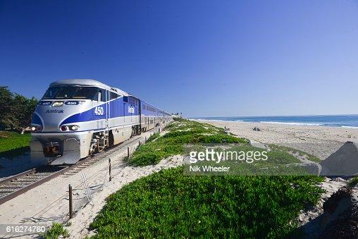 Amtrak Surfliner passenger train on tracks running alongside Pacific Ocean beaches near Santa Barbara on the west coast of California, USA : Stock Photo