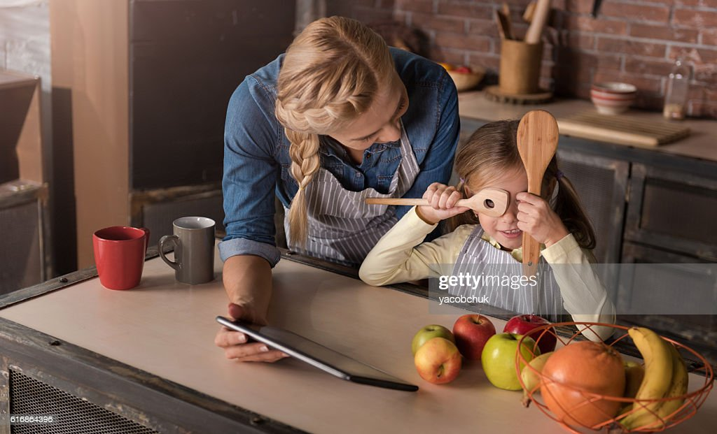 Amused girl having fun with her mother in the kitchen : Stock Photo