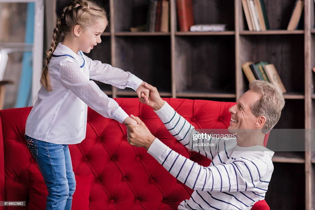 Amused little girl having fun with her grandfather : Stock Photo