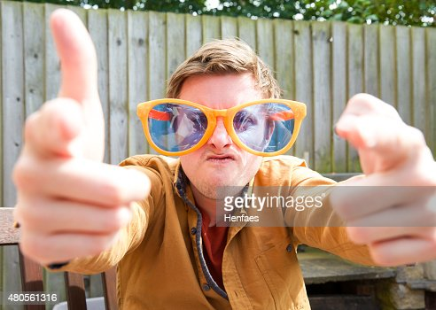 Amusing young male wearing very large sunglasses and pointing forward. : Stock Photo