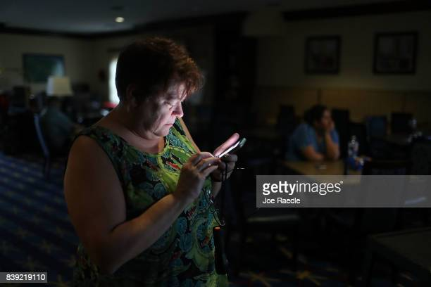 Amy Currin watches the weather news on her cell phone after the power went out at the TownePlace Suites hotel where she was taking shelter from...