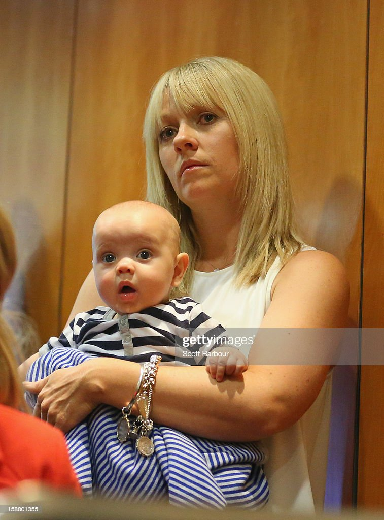 Amy Hussey, the wife of Michael Hussey of Australia holds her son Oscar as she watches her husband during at a press conference on December 30, 2012 in Melbourne, Australia. Mike Hussey has announced that the third Vodafone Test against Sri Lanka in Sydney will be his last Test for Australia.