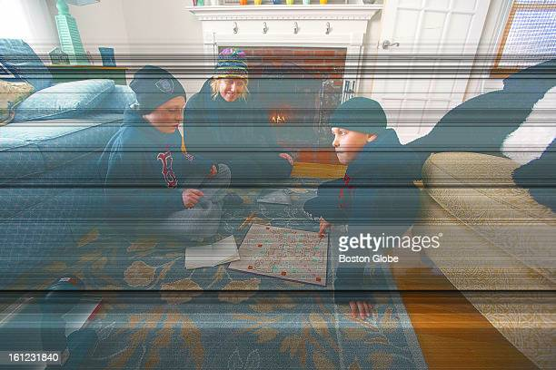 Amy Kelly wearing her winter coat watches with her sons John Kelly left and Matthew Kelly play Scrabble on their living room floor on Saturday Feb 9...
