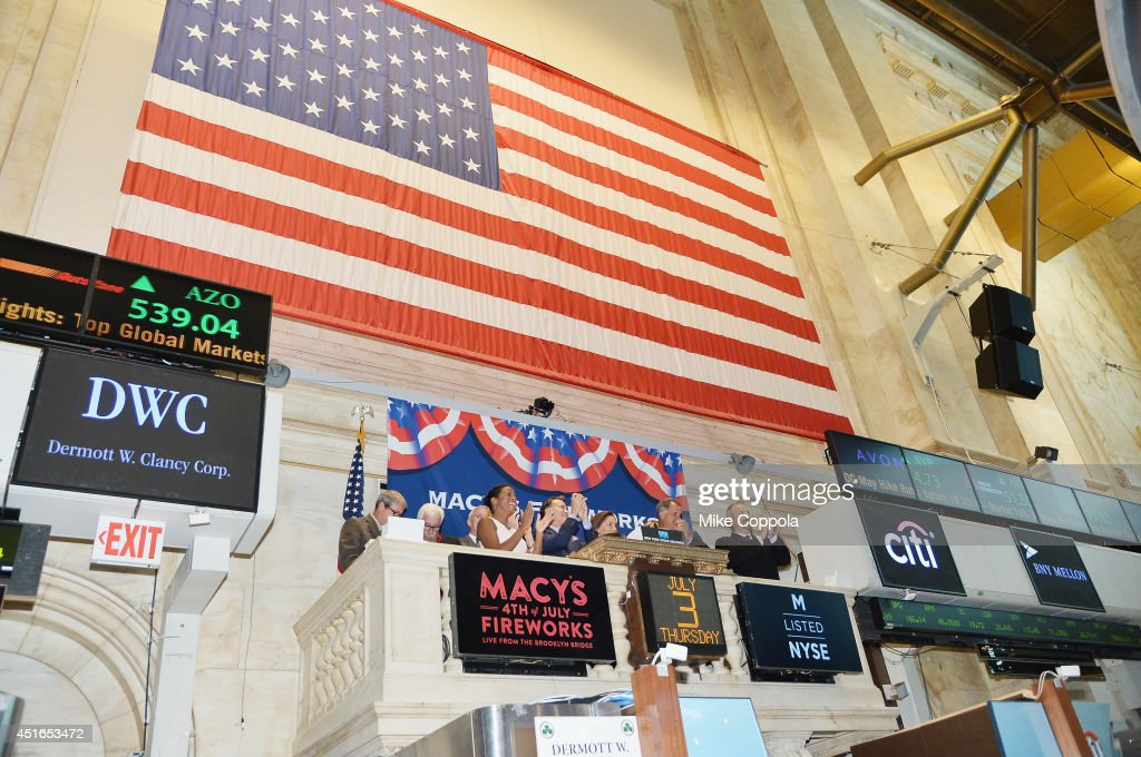 Amy Kule, Executive Producer of Macy's 4th of July Fireworks (7th from L) rings the closing bell at the New York Stock Exchange on July 3, 2014 in New York City.