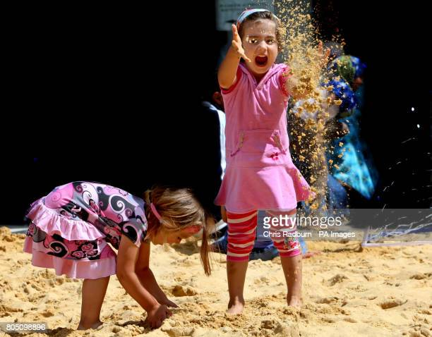 Amy Lelaand Fiona Memishi enjoy the beach in the Town Square of Barking Essex inspired by the Olympics and celebrating the birthday of the Games in...