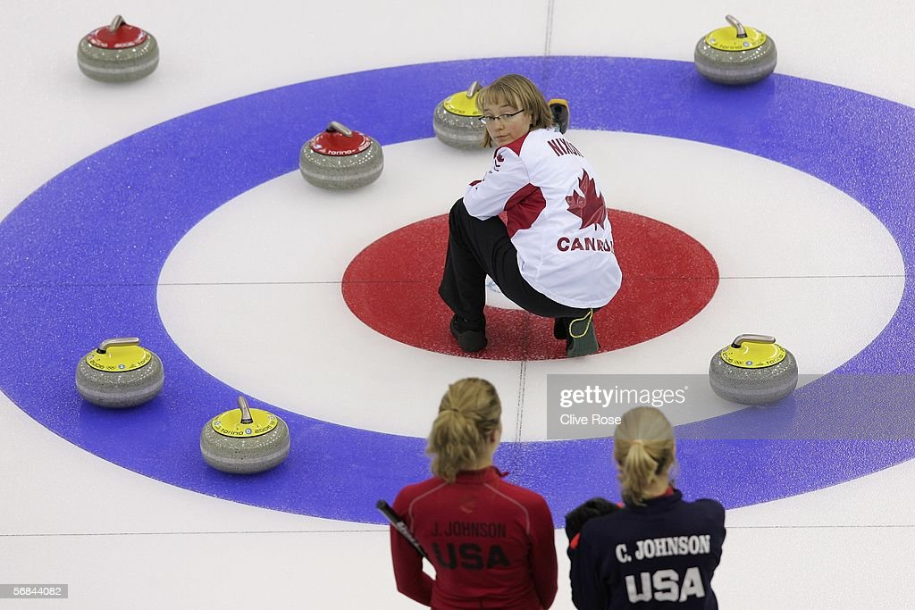 Amy Nixon of Canada turns to look at Cassie and Jamie Johnson of the United States during the Preliminary Round of the Women's curling between USA...
