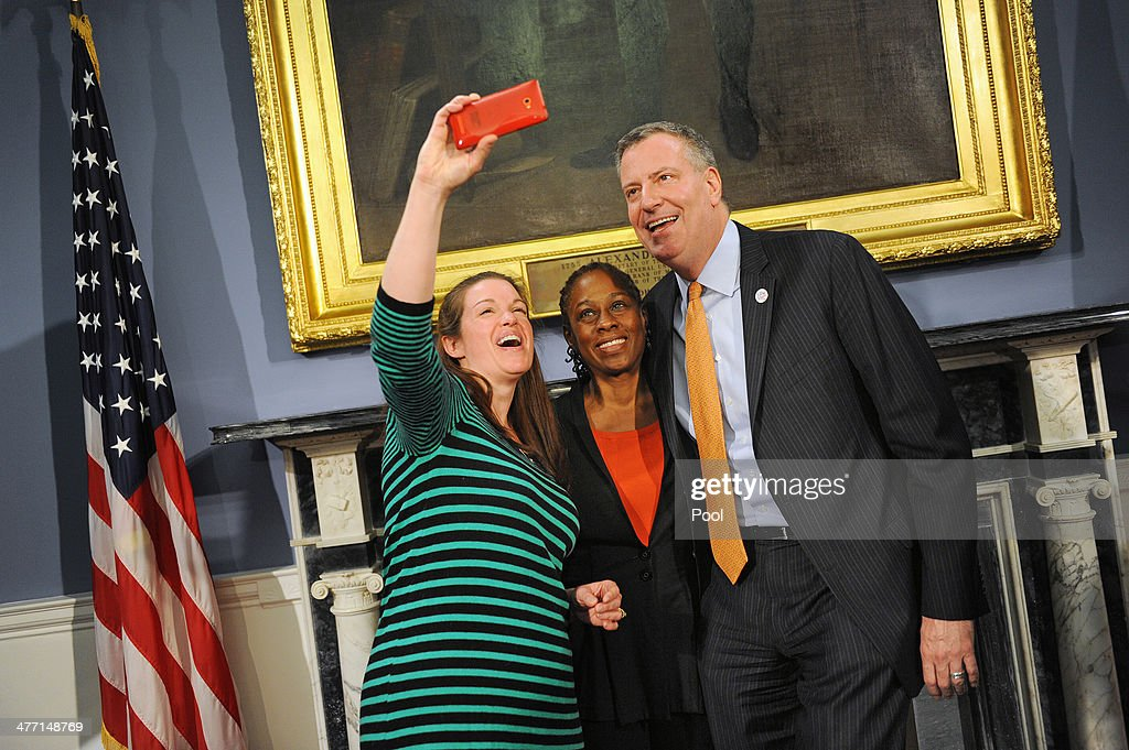 Amy Oztan of Selfish Mom takes a photo with Mayor Bill de Blasio and First Lady Chirlane McCray during a roundtable discussion with parent bloggers in the Blue Room of City Hall on March 7, 2014 in New York City. The roundtable discussion included topics about universal pre-K and after school programs .