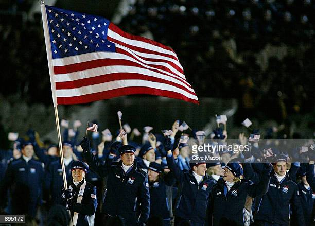 Amy Peterson a short track speed skater from the US Olympic team carries the US flag as she leads other US athletes during the Opening Ceremony of...