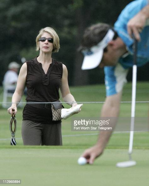 Amy Wilson left watches her husband pro golfer Mark Wilson place his ball on the second green during the first round of the Crown Plaza Invitational...