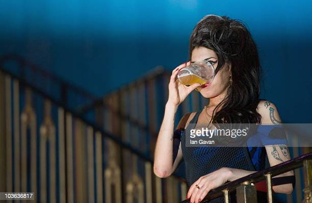 Amy Winehouse drinks a pint of lager as she watches The Libertines perform live at The Forum on August 25 2010 in London England