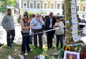 Amy Winehouse's father Mitch Winehouse and mother Janis Winehouse look at floral tributes left at Amy's house by fans on July 25 2011 in London...