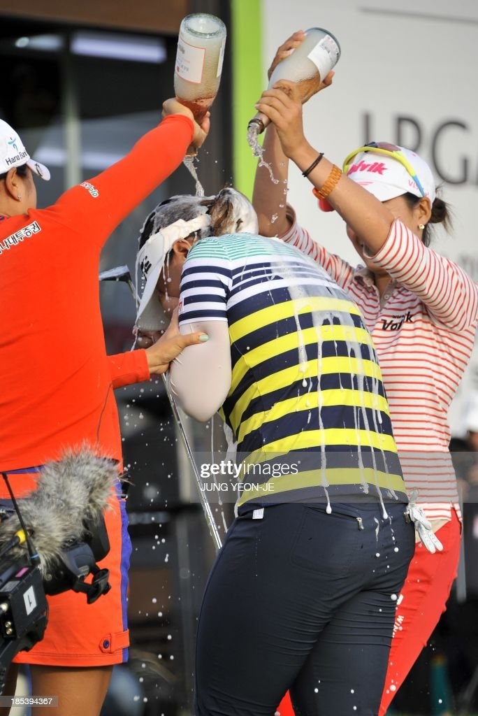 Amy Yang (C) of South Korea is showered with champagne after winning the LPGA KEB-HanaBank Championship golf event at the Sky72 Golf Club in Incheon, west of Seoul, on October 20, 2013. Yang won her first US LPGA title sinking a birdie in a playoff to capture the LPGA KEB-HanaBank Championship on home soil.