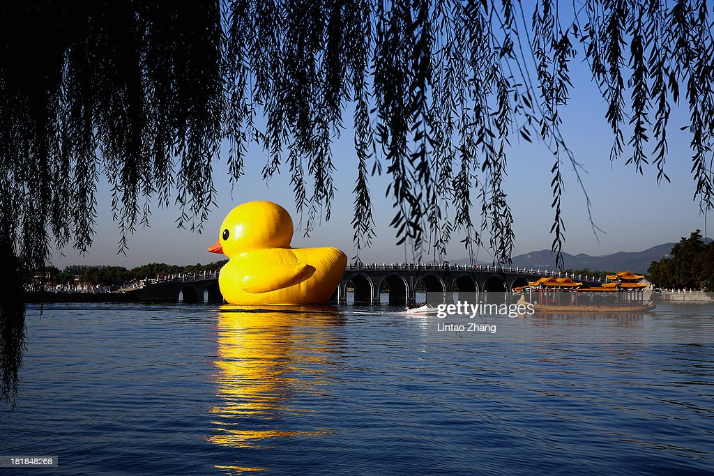 An 18-meter high rubber duck sits in the Summer Palace Kunming Lake on September 26, 2013 in Beijing, China. After touring 13 cities in 10 countries, the giant rubber duck designed by Dutch artist Florentijn Hofman will be in at Summer Palace from September 26 to October 26.