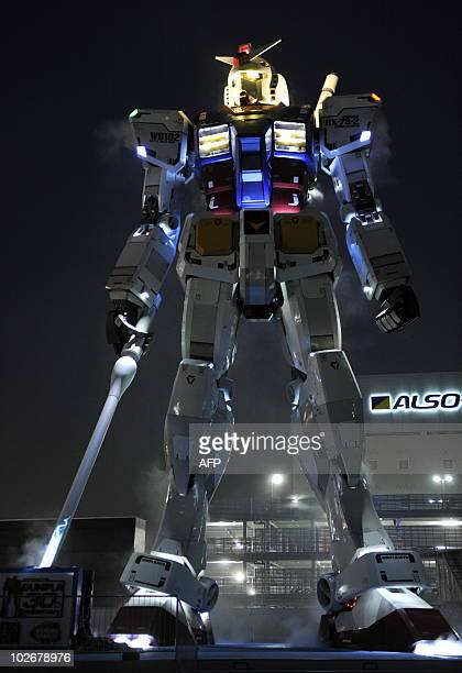 An 18metre tall statue of popular TV animation hero Gundam is lit up as vapors are expelled from its back at a park in Shizuoka city 150km west of...