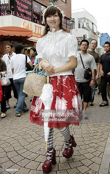 An 18yearold young Japanese woman wearing the latest fashion walks along a street in Tokyo's Harajuku fashion district 04 September 2004 AFP...