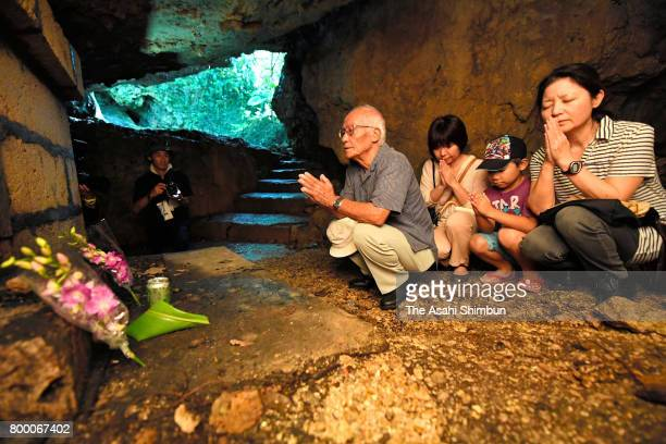 An 86yearold man and his relatives on June 23 offer prayers for his deceased elder brother in a cave beneath Kenji no To monument which is dedicated...
