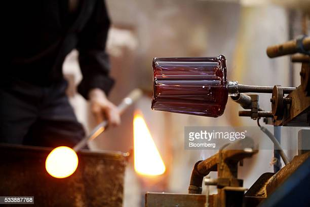 An Aalto style vase takes shape on the end of a glass blower's rod in the workshop at the Iittala Oyj glass factory operated by Fiskars Oyj in...