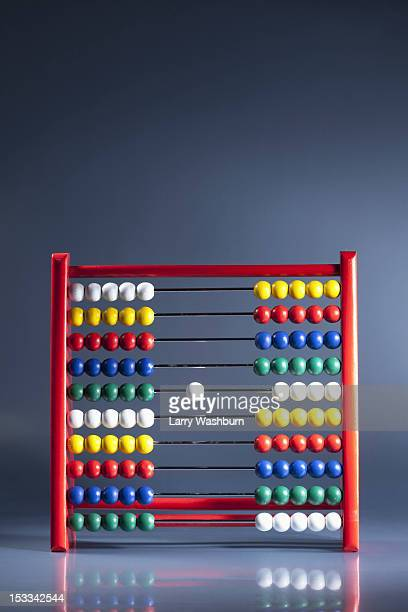 An abacus with neat rows of multi colored beads and a single white bead in the middle
