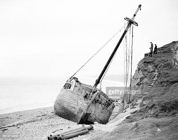 An abandoned boat lies on its side on the beach February 1934 P23069