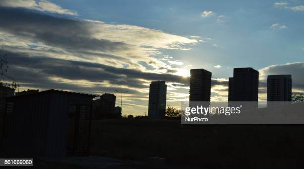 An abandoned cabin is seen in a wild field as the sun beams beyond tall residential buildings under construction in Ankara Turkey on October 15 2017...