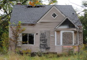 An abandoned home seen September 30 2013 in Detroit Michigan is decorated with a piece of fencing and graffiti which declares 'All I ever wanted was...