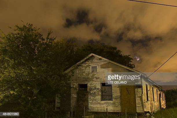 An abandoned house damaged by Hurricane Katrina in the eerie glow of streetlamps is seen in the lower Ninth Ward of New Orleans on August 15 2015 Ten...