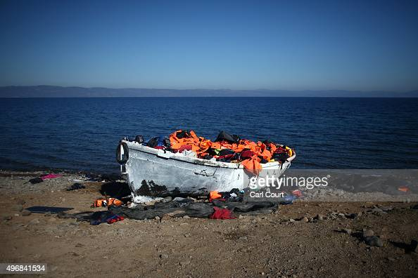 An abandoned migrant boat is filled with discarded life jackets after making the crossing from Turkey to the Greek island of Lesbos on November 12...