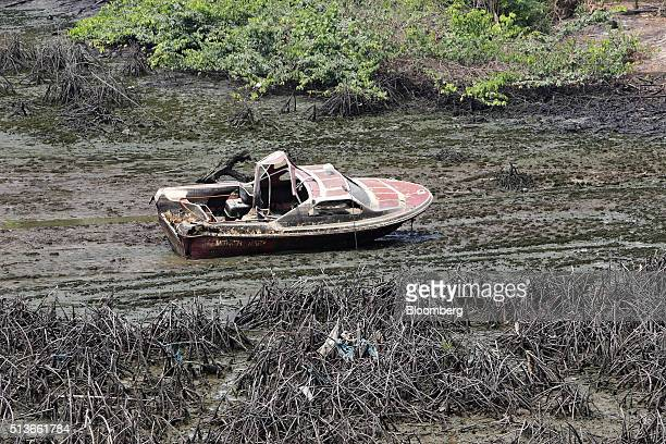 An abandoned motor boat sits in an oil polluted creek in Bodo Nigeria Wednesday Jan 13 2016 Twenty years after the oilpollution crisis in the Niger...