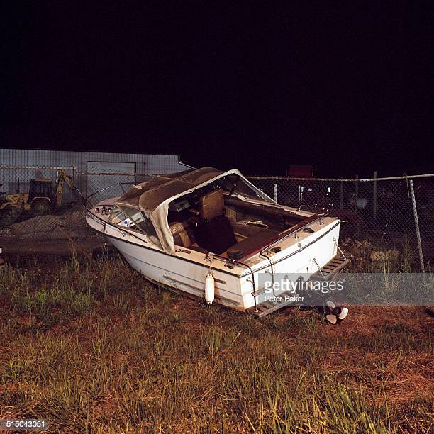 An abandoned motorboat in a vacant lot, night time