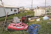 An abandoned skidoo and assorted rubbish alongside houses in the Inuit community of Shishmaref in the Chukchi Sea Alaska Shishmaref is home to 600...