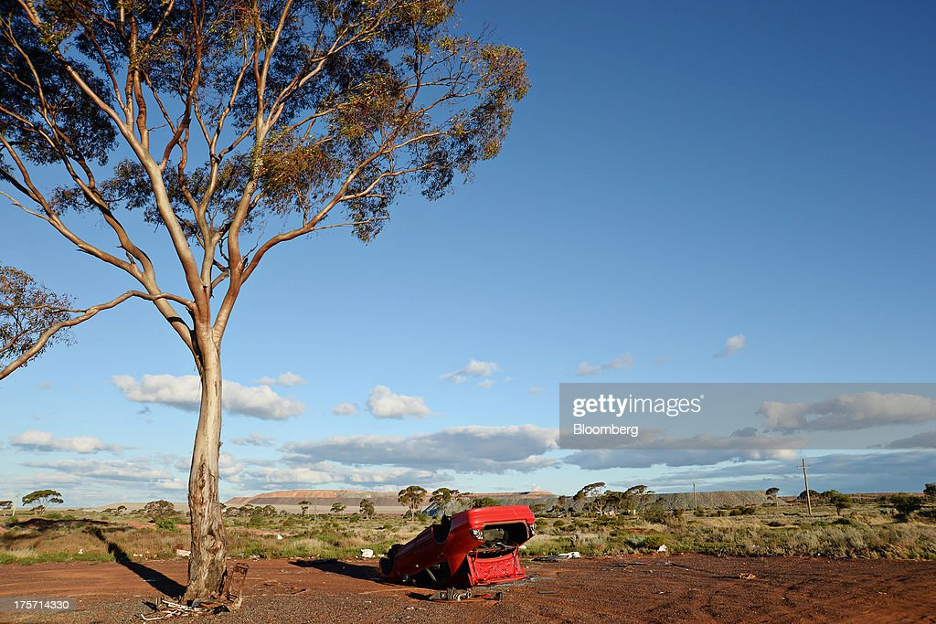 An abandoned upturned car sits in front of The Super Pit on the outskirts of Kalgoorlie, Australia, on Tuesday, Aug. 6, 2013. Kalgoorlie, a town in the Goldfields-Esperance region of Western Australia, is home to the annual Diggers & Dealers mining forum. Photographer: Carla Gottgens/Bloomberg via Getty Images