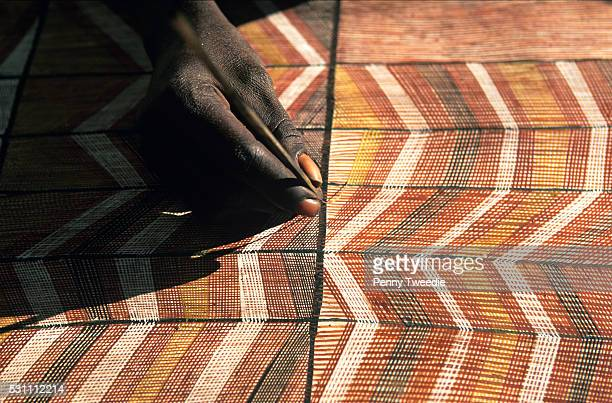An Aboriginal artist painting with natural ochres on carefully prepared stringy bark in the traditional way using a paint brush made of finely timmed...