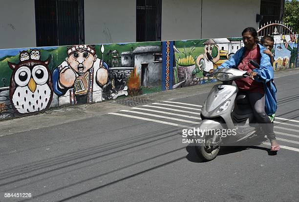An aboriginal woman rides a scooter with her son at a village in Taitung eastern Taiwan on July 2 2016 New president Tsai Ingwen the first Taiwanese...