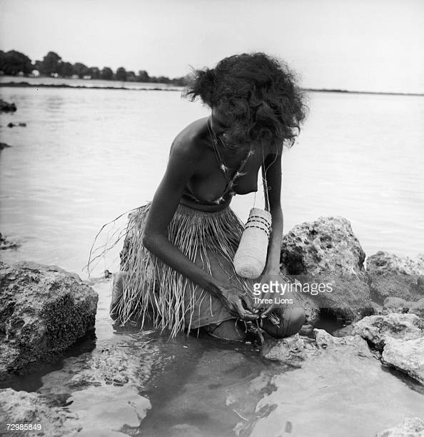 An Aborigine woman searches for shellfish to store in her woven dilly bag in Arnhem Land in the Northern Territory of Australia circa 1950