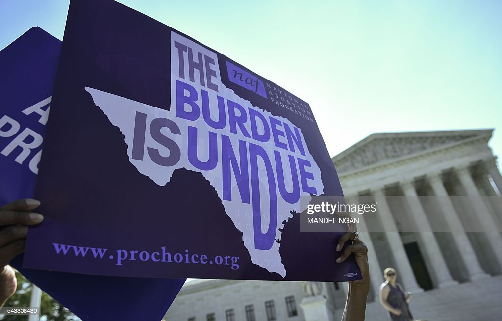 An abortion rights activist holds placards outside of the US Supreme Court before the Court struck down a Texas law placing restrictions on abortion clinics on June 27, 2016 in Washington, DC. The US Supreme Court on Monday struck down a Texas law placing a raft of restrictions on abortion clinics, handing a major victory to the 'pro-choice' camp in the country's most important ruling on the divisive issue in a generation. / AFP / MANDEL
