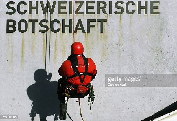 An abseiler is seen under a sign reading 'Swiss Embassy' after unveiling a banner carrying the Albert Einstein quote 'genuine democracy is...