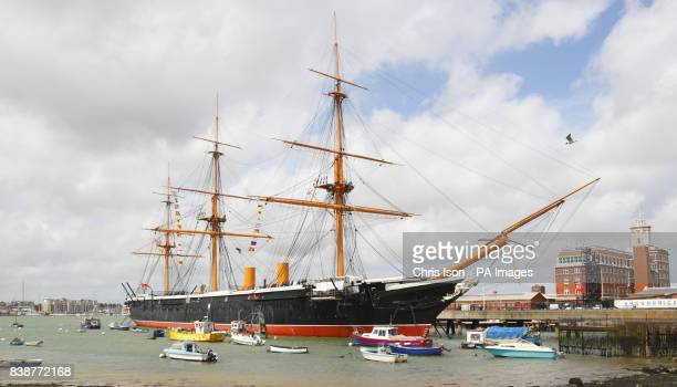 An abseiling engineer is a tiny speck in the middle of the rigging of HMS Warrior as he performs maintenance to the ropes of the 151 year old ship at...