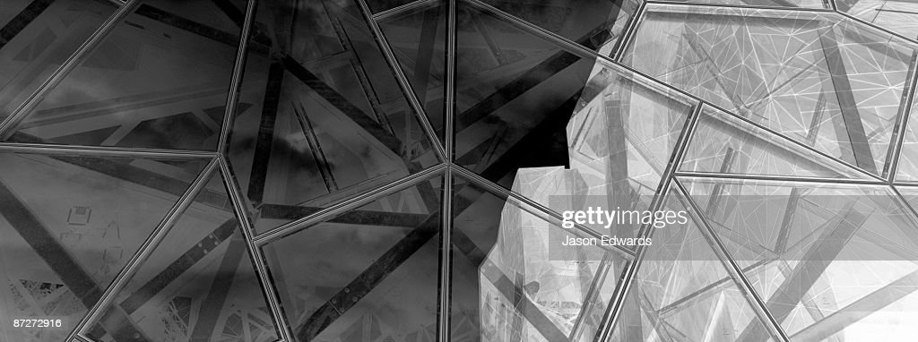 An abstract steel and glass facade reflects light and shadow equally. : Stock Photo