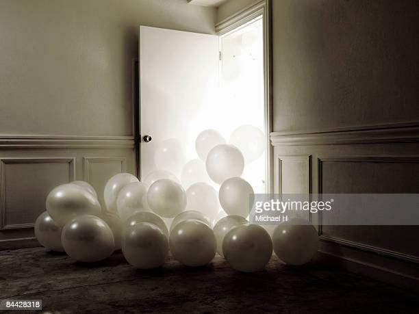 An abundance of white balloon overflow from door