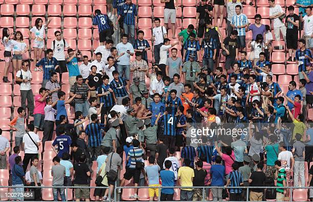 An AC Milan fan is stripped by Inter Milan fans during an Inter Milan training session at Beijing Workers Stadium on August 2 2011 in Beijing China