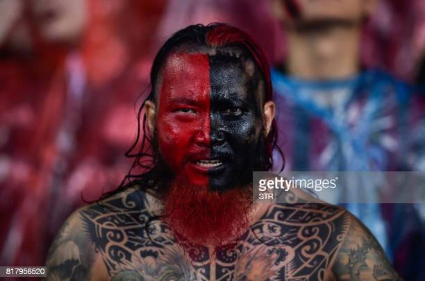 TOPSHOT An AC Milan supporter watches from the stands as the team plays Barussia Dortmund during their International Champions Cup football match in...