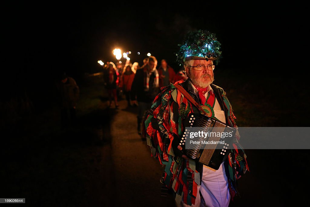 An accordion player from the Chanctonbury Ring Morris Men heads for a drink of cider after the Apple Howling ceremony at Old Mill Farm on January 5, 2013 in Bolney, England. In this ancient ritual villagers surround the oldest and largest tree in the orchard and evil spirits are driven out and good spirits are encouraged to produce a bountiful apple crop for the following year's cider drink.