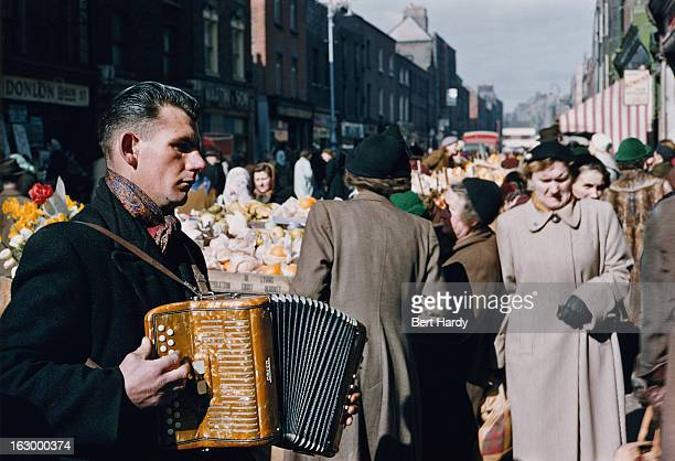 An accordionist playing at a street market in Dublin June 1955 Original publication Picture Post 7808 Dublin pub 18th June 1955